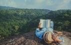 Turista lê um livro durante as férias, relaxando nos penhascos rochosos no Moutain, Tailândia