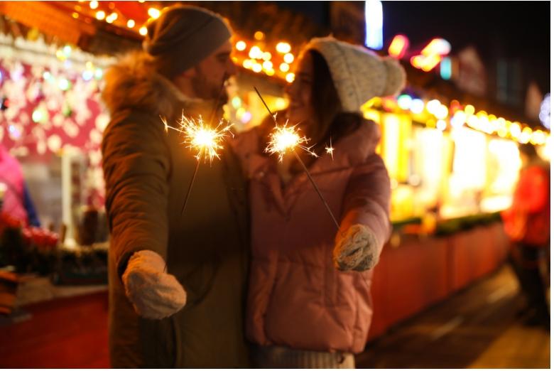 Casal desfruta de um passeio num Mercado de Natal