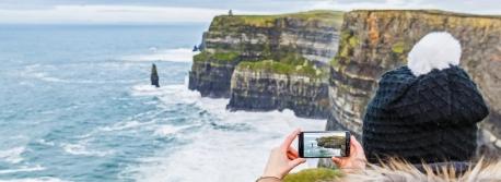 Turista nas Escarpas de Moher, na Irlanda
